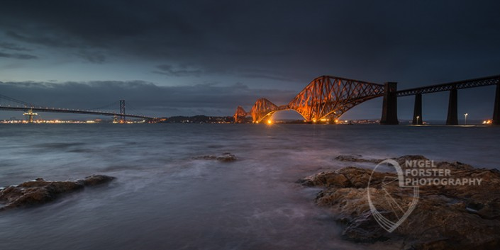 Forth Rail Bridge at Dusk, Scotland. An example of Landscape, Architecture, Travel and Tourism Photography, using dramatic lighting and striking composition by Nigel Forster ABIPP. Commission Nigel Forster ABIPP to capture your business, event, attraction or location with dramatic use of light and striking composition.