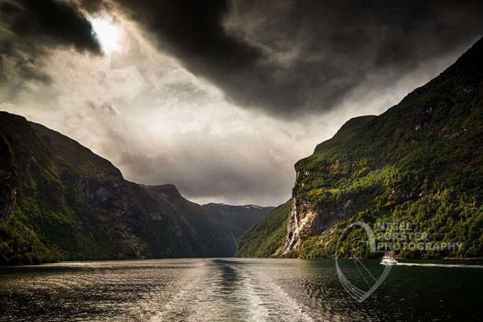 Seven Sisters Waterfall, Gerainger Fjord, Norway. An example of Landscape, Architecture, Travel and Tourism Photography, using dramatic lighting and striking composition by Nigel Forster ABIPP. Commission Nigel Forster ABIPP to capture your business, event, attraction or location with dramatic use of light and striking composition.