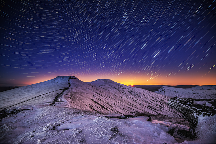 Star trails above a snow covered Pen y Fan in the Brecon Beacons